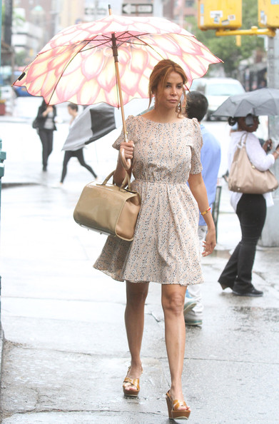 Kara Young wasn't thrown off by the rain, she just made it better when she carried this charming umbrella with a light floral dress and beige bag.