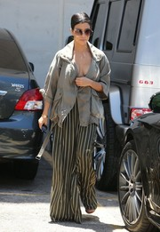 Kourtney Kardashian watched 'The Phantom of the Opera' wearing wide-leg striped pants and a matching bra top.