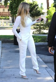 Khloe Kardashian matched her top with a pair of tailored white slacks.