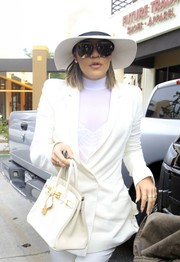 Khloe Kardashian topped off her all-white look with a wide-brimmed hat.