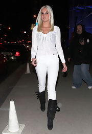 Karissa toughened up her pristine white street attire with black buckled knee high boots.
