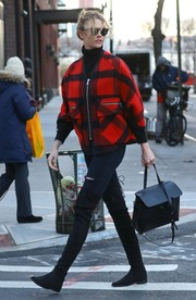 Karlie Kloss brightened up the pavement with her red and black Esprit by Opening Ceremony wool poncho that she paired with Soelae Sunday Somewhere sunnies while out in New York City.
