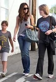 "Kate looks cool and casual while strolling with her blue leather ""Giant City"" handbag. This designer bag is great for everyday style, like Kate's casual jeans and tank look."