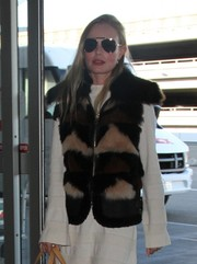 Kate Bosworth teamed aviator shades with a fur vest and an LWD for her airport look.