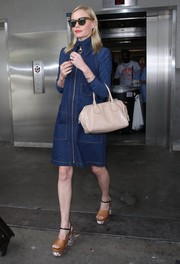 Kate Bosworth completed her airport look with a nude leather bowler bag, also by Prada.