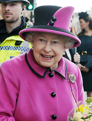 Queen Elizabeth II wore this black and pink hat with her matching ensemble while out with the Duchess in Leicester.