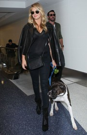 Kate Upton caught a flight at LAX wearing an edgy all-black leather jacket and skinny jeans combo.