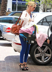 Katherine Heigl had her hands full but still managed to pull off a sexy stylish look in tight blue jeggings and shiny black strappy heels.