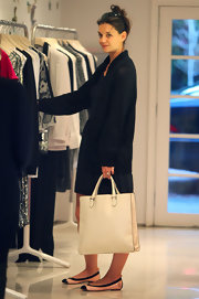 Katie Holmes went shopping in chic ballet flats. She paired the cap toe flats with a black sweater and cream tote.