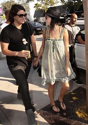Katy's cute black, patent leather, t-strap sandals look darling with her bohemian sun dress.