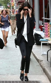 Kendall Jenner contrasted her elegant jacket with edgy studded and ripped jeans by Etienne Marcel.
