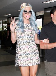 Kesha looked more like she was attending a costume party than catching a flight with her round sunnies, floral mini, and headband combo.