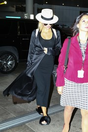 Khloe Kardashian looked sultry in a body-con black tank dress by Mystylemode while catching a flight from Miami.
