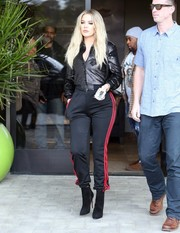 Khloe Kardashian went sporty on the bottom half with a pair of Adidas training pants.