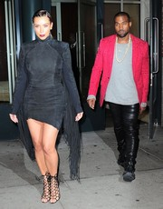 Kim Kardashian looked dramatic in a suede LBD with ankle-grazing fringes on the sleeves as she headed out to Kanye's concert.