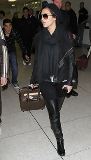 Kim wears a black pashmina with her thigh-high boots at the LAX airport.