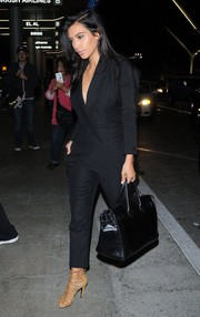 Kim Kardashian caught a flight at LAX looking ultra stylish in a black tuxedo-style jumpsuit by Saint Laurent.
