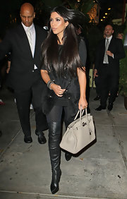 Kim Kardashian showed off one of her many Birkin bags while leaving dinner with her family in LA.