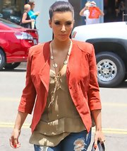 Kim Kardashian paired her burnt orange suede blazer with a layered gold chain necklace with Chanel pendants.