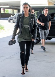 Kim Kardashian sealed off her edgy look with ripped black jeans by Paige.