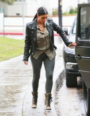 Kim Kardashian was sexy-edgy in gray Alaia leggings teamed with a leather jacket and studded boots while out in Brentwood.