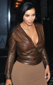 Kim Kardashian sizzled in a cleavage-baring brown leather jacket by Givenchy while out to dinner.