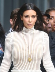 Kim Kardashian headed out in New York City wearing a classic gold pendant to pair with her knit dress.