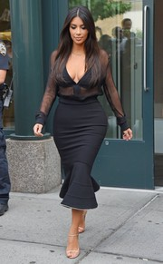 Kim Kardashian put plenty of skin on show in a sheer black Givenchy blouse while out in New York City.