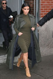 Kim Kardashian sheathed her curvy figure in a tight green turtleneck dress from the Kardashian Kollection for a day out in NYC.