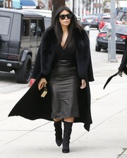 Kim Kardashian teamed her coat with a black Balmain leather skirt for an edgy-glam finish.