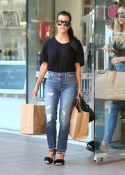 Kourtney Kardashian dressed down in a black tee by Frame and a pair of distressed jeans for a day of shopping.