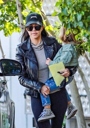 Kourtney Kardashian got some sun protection from a Yeezy baseball cap and a pair of shades.