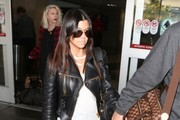 Couple Kourtney Kardashian and Scott Disick arriving on a flight at LAX airport in Los Angeles, California on December 3, 2013.
