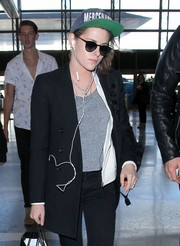 Kristen Stewart accessorized with a Mercenaries trucker hat and a pair of shades for a flight.