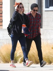 Kristen Stewart completed her outfit with red suede sneakers by Adidas.