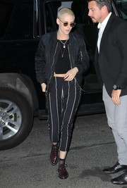 Kristen Stewart teamed striped pants by Brunello Cucinelli with a crop-top and a bomber jacket for a night out.