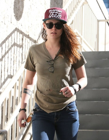 Kristen Stewart accessorized with an 'Us Versus Them' trucker hat while headed to a meeting.