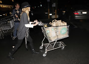 Kristin shopped in a pair of double-buckled black leather boots with black leggings, an oversized sweater and a fedora hat.