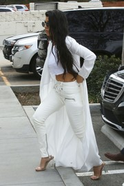 Kourtney Kardashian teamed her top with white lace-up skinny pants by Unravel.