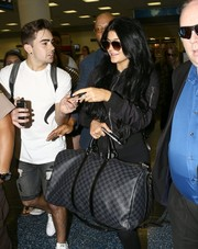 Kylie Jenner arrived on a flight in Miami carrying a Louis Vuitton Damier Graphite duffle.