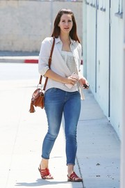 Lana Del Rey visited a studio in Santa Monica wearing skinny jeans and a white button-down layered over a mesh top.