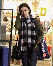 Lily Collins styled a plain green sweater with a black-and-white checkered scarf for a day out in West Hollywood.