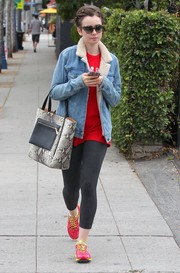 Lily Collins spruced up her casual look with a snakeskin-print tote by Vince Camuto.