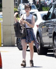 Lily Collins topped off her shopping outfit with an oversized leather bag by Prada.