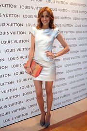 Rebecca wears a metallic cocktail dress with a colorful clutch.