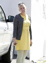 Busy Philipps winterized a sunny yellow dress with a gray cable knit cardigan.