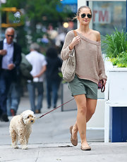 Minka Kelly walked her dog in New York City's Soho district wearing a beige crewneck sweater that was loose enough to wear off one shoulder.