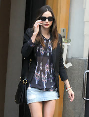 Since she bared her legs in a short denim skirt, Miranda Kerr kept her top half covered up in a blouse and black blazer.