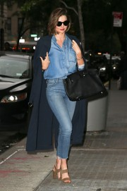 Miranda Kerr styled her casual look with tan broad-strap sandals by Manolo Blahnik.