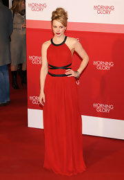 Rachel looks ravishing in a lipstick red evening dress with a leather neckline and wrap around belt.